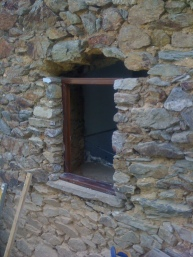 Window in position and stonework being rebuilt using lime mortar sympathetic to the original building.