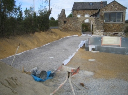 A membrane is laid to help suppress weeds which is then covered with gravel.