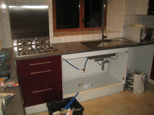 The tiles are grouted and cut-outs are made in the worktop for the appliances.