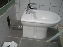 Sliding the Bidet onto its hidden waste pipe.