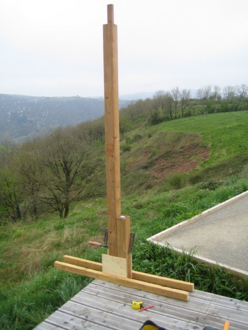This is the first post. The posts that run along the back edge are mounted through the deck and bolted to a support beam that runs along the edge. These will provide a strong support for the structure. Note the use of a jig to hold the post upright whilst it is bolted. Jigs like this are essential when you work alone.